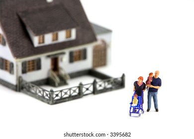 A miniature model home with a family in front. The focus is on the family and the home is out of focus due to shallow depth of field. Isolated on white background.