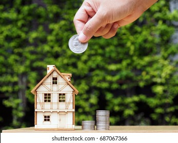 Miniature Model House and Stack Coins on Table with Blurred Green Background : Real Estate Investment, Insurance, Mortgage, Home Loan, Saving Money, Energy Efficient Home, Cost, and Expense Concept