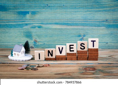miniature model of house and wooden letter text: invest