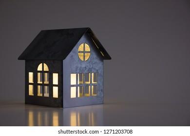 Miniature model metal house on a dark background