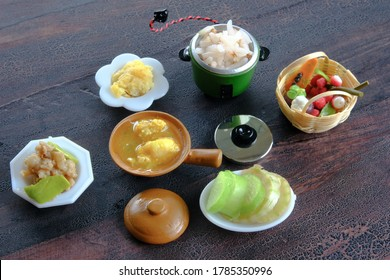 Miniature model, Thai southern food in the brown clay pot, stir-fried stink bean with pork, fried eggs, vegetables and fruits on wood background, selective focus.