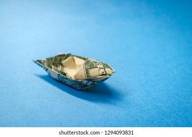 Miniature money dollar bill origami yacht conceptual metaphor