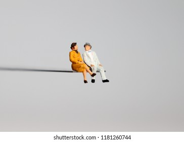 A miniature old age couple sitting on the edge of a precipice.