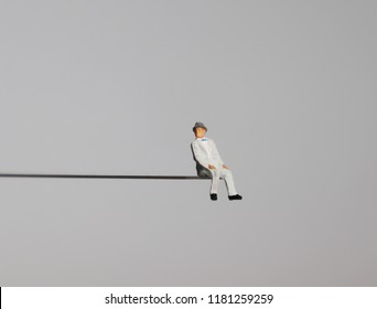 A miniature old age man sitting on the edge of a precipice.