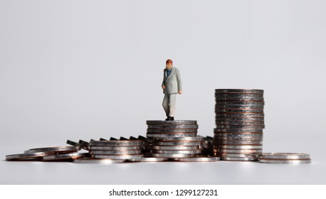 A miniature old age man walking on a pile of coins.