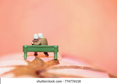 miniature of an old couple in love sitting on a bench
