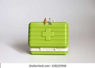 A miniature old couple sitting on a green medicine chest.