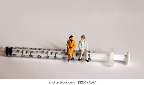 A miniature old couple sitting on a syringe. Concepts on the importance of health care for the elderly.