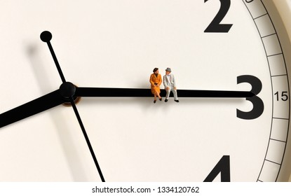 A miniature old couple sitting on a clock's needle.
