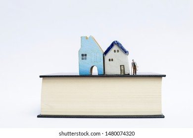Miniature old man carry grocery bag with two miniature house on thick book isolate on white background, eldery home, eldery care service, real estate and property business