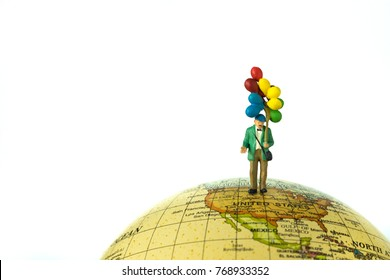 Miniature old man holding balloons standing on globe using as happy senior retirement or world peace concept with copy space.