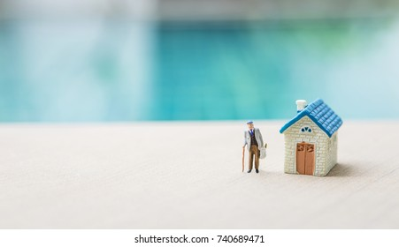 Miniature old man with miniature new house, elderly home concept