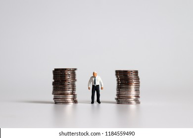 A miniature old man standing among a pile of coins.