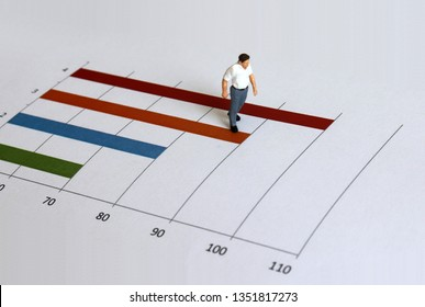 A miniature old man walking on a bar graph.