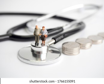 Miniature old people standing on medical stethoscope with coins stack on white background, Retirement planning, Emergency plan, Life insurance Concept.
