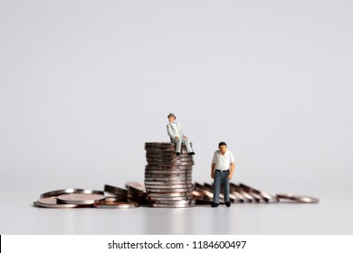 A miniature old-age man sitting on a pile of coins and a miniature old-age man standing next to him.