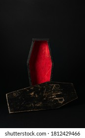 Miniature open black-red coffin on a black background. Festive halloween concept. A place for your product