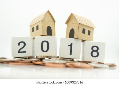 Miniature paper house on wood number 2018 and coins with copy space using as background business, new year, real estate, property concept.