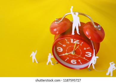 miniature paper people with  a large clock, an alarm clock on a yellow background. The concept of time and man