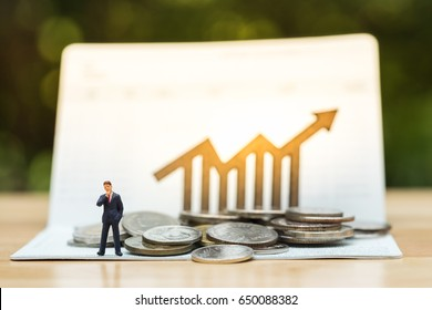 Miniature peolple standing in front of coins stack on bankbook with bar chart with arrow line wooden icon. Concept of money saving, financial, personal loan,retirement,insurance, business plan.