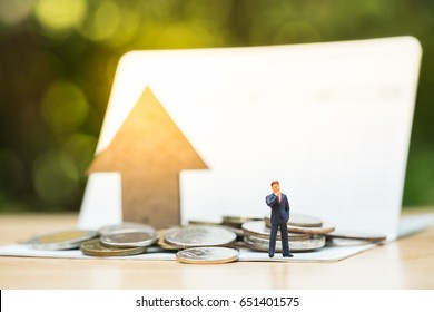 Miniature peolple standing in front of coins stack on bankbook with arrow wooden icon. Concept of money saving, financial, personal loan,retirement,insurance, business plan.