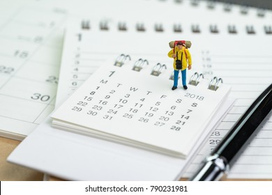 Miniature people, backpacker man figure standing on 2018 calendar with pen using as travel planning or vocation, holiday plan.