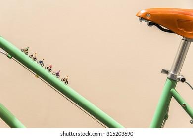 Miniature people biking on vintage bike