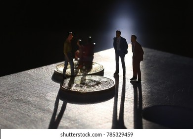 Miniature people with bitcoins, symbolising exchanges, trades in a dark background