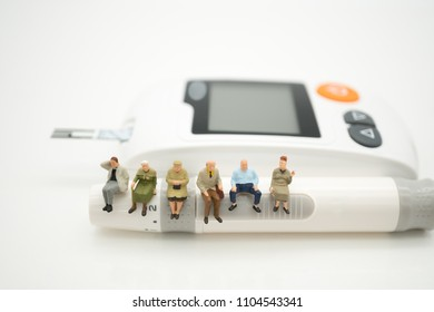 Miniature people with blood glucose meter, lancet using as background Health care medical and check up, diabetes, glycemia, and people concept.