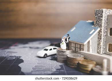 Miniature people bride and groom with coins money at home , Success family conceptual.