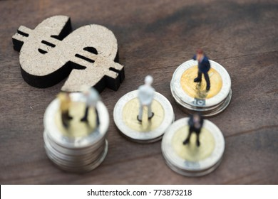 Miniature people: business man making decision on world map in front of wooden dollar sign and coins stacks, success, dealing, greeting and partner concept. Flat lay