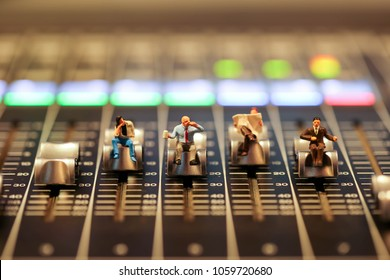 Miniature people : business man sitting on Professional audio mixing console with faders and adjusting knobs,TV equipment ,sound musical mixing&engineering concept background