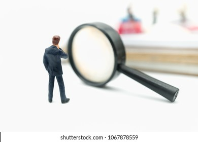Miniature people: Business man standing on white background with binoculars using as recruitment choice of the best suited employee, HR, HRM, HRD, job recruiter concepts.