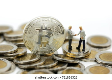 Miniature people : business man standing with bitcoins . success, dealing, greeting ,money , business , partner concept.