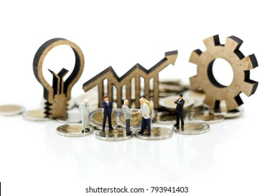 Miniature people: business man standing on coins stacks with idea lamp icon as background, success, dealing, partner concept.