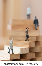 Miniature people: Business man walking grow up on wood block using as background Choice of the best suited employee, HR, HRM, HRD, job recruiter, business concepts.