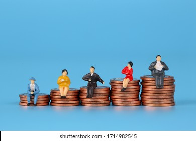 Miniature people - Business people are sitting on the coins, Business Growth concept, blue background