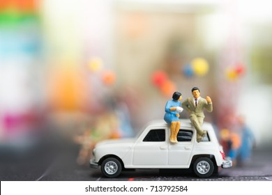 Miniature people : businesses team sitting on car with copy space using as travel around the world, business trip traveler adviser agency or online world wide marketing concept.