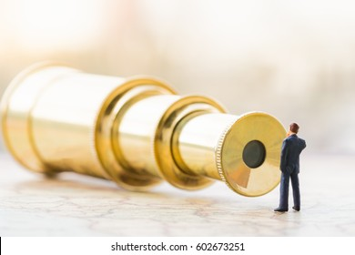 Miniature people : businessman figure standing on vintage map in front of monocular and Searching the opportunity concept.