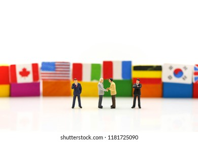 Miniature people : Businessman with international flag using for concept of United Nations Day.