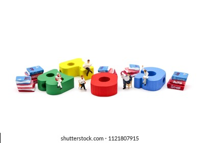 Miniature people : businessman reading a book sitting on Colorful alphabet,education and social background concept.