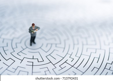 Miniature people: Businessman reading book and standing on center of maze using as background business finding solution, problem solving and challenge concept.