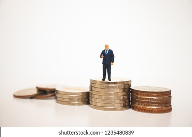 Miniature people, businessman show good job symbol on stack coins using as business and financial concept