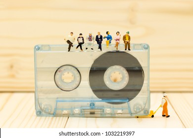 Miniature people: Businessman sit and reading newspaper  on Compact Cassette. Image use for music , business concept.