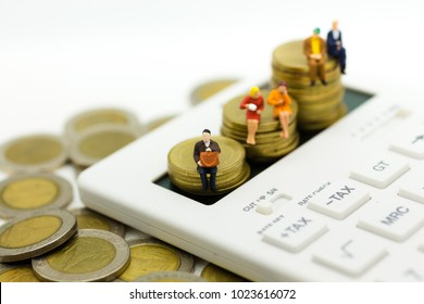 Miniature people: Businessman sitting on stack of coins with calculator, calculation tax monthly/yearly. Image use for Tax calculation every year for everyone.
