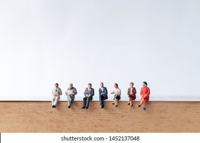 Miniature people : Businessman sitting on old book  with copy space on white background