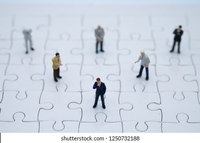 Miniature  people businessman stand on white jigsaw. Picture use for business vision concept.business planning using as background and Strategy concept with copy space for your text