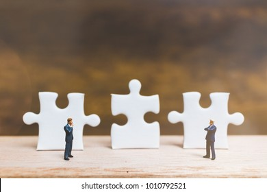 Miniature people: Businessman standing on jigsaw with wooden background : Business concept.