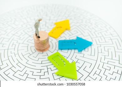 Miniature people: Businessman standing on stack of coins at front of arrow pathway choice using as Business decision concept.