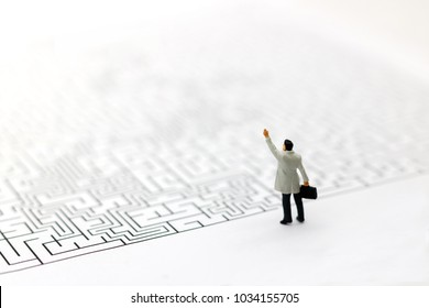 Miniature people: Businessman standing on start of maze. Concepts of finding a solution, problem solving and challenge.